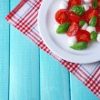 Caprese salad with mozarella cheese, tomatoes and basil on plate, on wooden table background — Stock Photo #45633047