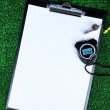 Sheet of paper, stopwatch and whistle on grass close-up — Stock Photo #45634053