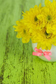 Beautiful chrysanthemum flowers in vase on wooden table close-up — Stock Photo