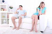 Young man and woman  conflict sitting on sofa argue unhappy, on home interior background — Stock Photo