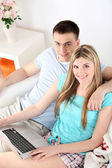 Loving couple sitting with laptop on sofa, on home interior background — Stockfoto