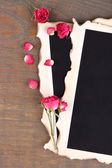 Blank photo paper and beautiful pink dried roses on wooden background — 图库照片