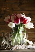 Beautiful tulips in glass jug on wooden background — Stock Photo