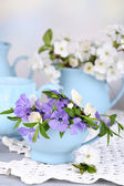Beautiful spring flowers in cups on wooden table — Stock Photo
