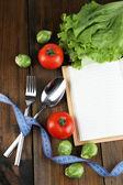 Posate legato con nastro di misurazione, libro con verdure su fondo in legno — Foto Stock