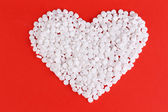 Heart of pills on red background — Stock Photo