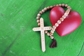 Heart with rosary beads on wooden background — ストック写真