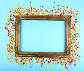 Photoframe with confetti on blue background — Stock Photo