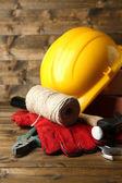 Composizione con casco, guanti in pelle, strumenti e decorativo casa su fondo di legno — Foto Stock