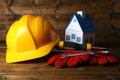 Composition with safety helmet, leather gloves, tools and decorative house on wooden background — Stock Photo