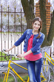 Beautiful young woman with bicycle outside — Stock Photo