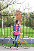 Beautiful young woman with bicycle outdoors — Stock Photo