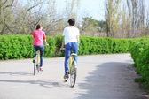 Pareja joven montando en bicicleta en el parque — Foto de Stock