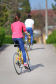 Young couple riding on bicycles in park — Stock Photo