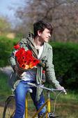Ung man med blommor på cykel i park — Stockfoto