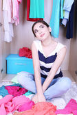 Beautiful young woman sitting on floor near wardrobe in room — Stock Photo