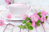 Beautiful fruit blossom with cup of tea on table on light background — Stock Photo