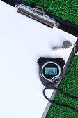 Sheet of paper, stopwatch and whistle on grass close-up — Stock Photo