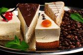 Sortiment av bitarna av kakan, på mörk bakgrund — Stockfoto