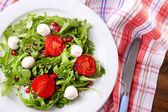 Salade verte avec la roquette, les tomates, les boules de fromage mozzarella et sésame sur plaque, sur fond de bois — Photo