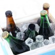 Ice chest full of drinks in bottles on color napkin, isolated on white — Stock Photo #45905951