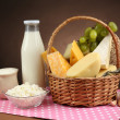 Basket with tasty dairy products on wooden table, on dark brown background — Stock Photo #45906829