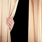 Hand opening curtain on black background — Stock Photo