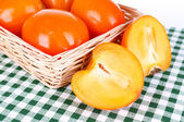 Ripe persimmons in wicker basket on table close-up — Stock Photo