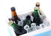 Ice chest full of drinks in bottles on color napkin, isolated on white — Stock Photo