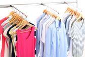 Různé šaty na ramínka, na šedém pozadí — Stock fotografie