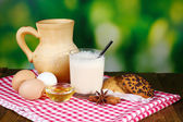 Eggnog with milk and eggs on tablecloth on natural background — Stock Photo