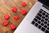 Computer with red hearts on table close up — Stock Photo