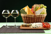 Basket with different cheese and glasses of wine on wooden table, on dark black background — Stock Photo
