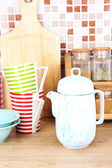 Tableware in kitchen on table on mosaic tiles background — Stock Photo