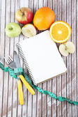 Cutlery tied with measuring tape and notebook with fruits on wooden background — Stock Photo