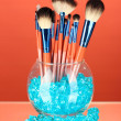 Make-up brushes in a bowl with stones on red background — Stock Photo #46188149