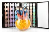 Make-up pinsel in eine schale mit steinen auf palette mit schatten-hintergrund — Stockfoto