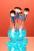 Make-up brushes in a bowl with stones on red background — Stock Photo