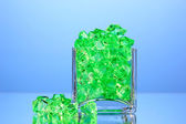 A glass with green decorative stones on blue background close-up — Stock Photo