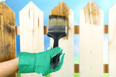 Applying protective varnish to wooden fence, on bright background — Stock Photo