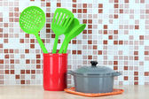 Cooking utensils and pan in kitchen on table on mosaic tiles background — Stock Photo