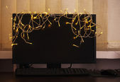 Laptop with garland, on office interior background — Stock Photo