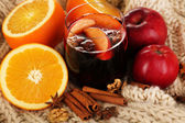 Fragrant mulled wine in glass on knitted scarf close-up — Stock Photo