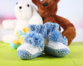 Crocheted booties for baby and toys,on color background — Stock Photo