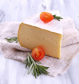 Tasty Camembert cheese with rosemary and tomato, on wooden table — Stock Photo