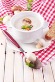 Mushroom soup in white pot, on napkin, on wooden background — Stock Photo