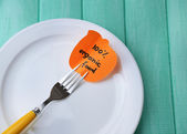Note paper with message  attached to fork, on plate, on color wooden background — Stock Photo