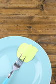 Empty note paper attached to fork, on plate, on color wooden background  — Stock Photo
