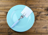 Empty note paper attached to fork, on plate, on color wooden background  — Stockfoto