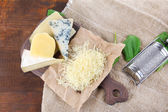 Different Italian cheese on sackcloth, on wooden background — Stock Photo